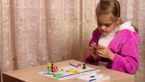 Het meisje beeldhouwt ambachten aan de andere kant van plasticinezitting bij een lijst van de lege ruimte stock video