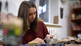 Het meisje beeldhouwt een mok van klei stock video