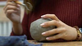 Het meisje beeldhouwt een mok van klei stock footage