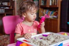 Het meisje beeldhouwt uit zand in haar ruimte Stock Fotografie
