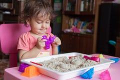 Het meisje beeldhouwt uit zand in haar ruimte Stock Afbeeldingen