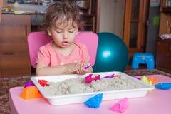 Het meisje beeldhouwt uit zand in haar ruimte Stock Foto