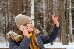 Het meisje begroet iemand die met de hand, op de telefoon in de winter in openlucht spreken royalty-vrije stock afbeelding