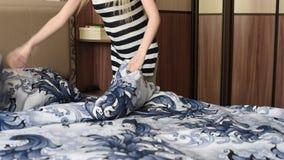 Het meisje behandelt het bed met nieuw linnen, tegen de achtergrond van andere furnitur stock video