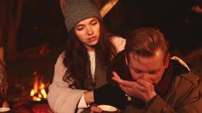 Het meisje behandelt de ziektemens met rode neus, zijn zij buiten in de herfstpark op schemering, drank hete thee dichtbij vuur H stock videobeelden