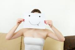 Het meisje behandelt haar gezicht met blije die het plagen glimlach op papier wordt getrokken Stock Afbeeldingen