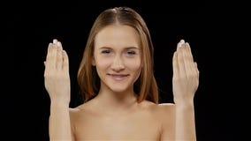 Het meisje behandelt haar gezicht met haar handen, en toont dan zijn glimlach met steunen zwart Langzame Motie stock videobeelden