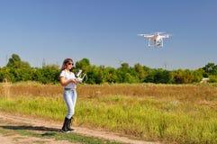 Het meisje beheert quadrocoptersgebied stock foto