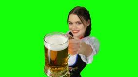 Het meisje in Beiers kostuum biedt een glas bier aan Het groene scherm stock video
