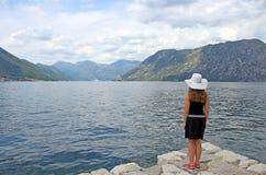 Het meisje bekijkt de baai van Kotor van het cruiseschip op zee stock foto