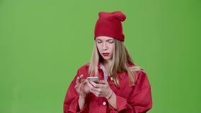 Het meisje bekijkt de beelden in de telefoon en toont duimen Het groene scherm stock footage