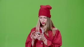 Het meisje bekijkt de beelden in de telefoon en toont duimen Het groene scherm Langzame Motie stock videobeelden
