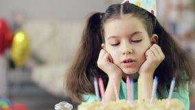 Het meisje bekijkt de cake stock videobeelden