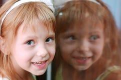 Het meisje bekijkt de camera en het glimlachen stock foto's