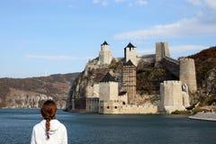 Het meisje bekijkt de Golubac-vesting op de rivier van Donau stock afbeelding