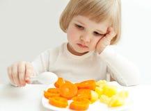 Het meisje bekijkt de groenten Stock Fotografie