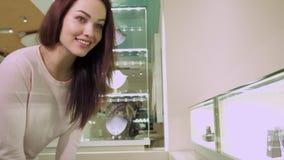 Het meisje bekijkt de het winkelen vertoning met juwelen stock video