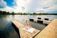 Het meisje bekijkt de rivierzitting op het dok royalty-vrije stock afbeeldingen