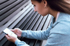 Het meisje bekijkt de telefoon op de straat Royalty-vrije Stock Foto