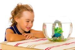 Het meisje bekijkt de vis die in het aquarium drijft stock afbeelding