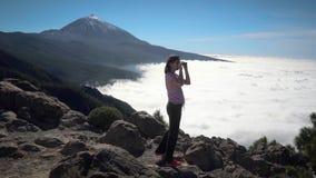 Het meisje bekijkt de wolken en de vulkaan stock videobeelden