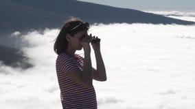 Het meisje bekijkt door verrekijkers wolken stock footage