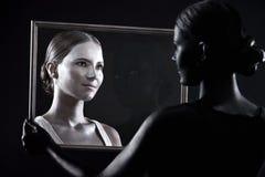 Het meisje bekijkt haar tweeling door het glas Stock Afbeelding