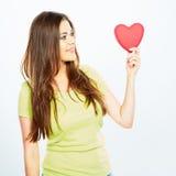 Het meisje bekijkt het hart dat in zijn hand houdt Stock Afbeeldingen