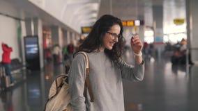 Het meisje bekijkt het horloge in de luchthavenzitkamer stock videobeelden