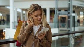 Het meisje bekijkt iets in haar telefoon die zich met het winkelen zakken op haar schouder in de wandelgalerij bevinden stock footage