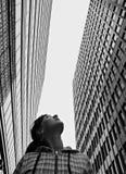 Het meisje bekijkt upwards high-rise gebouwen Stock Afbeelding