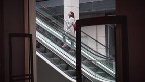 Het meisje beklimt de roltrap in de opslag stock videobeelden