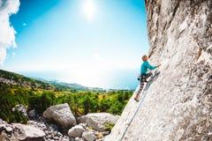 Het meisje beklimt de rots Royalty-vrije Stock Foto