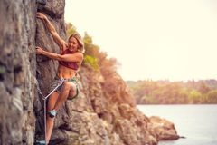 Het meisje beklimt de rots Stock Afbeelding