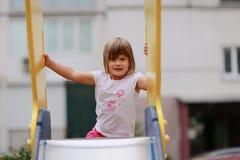 Het meisje beklimt op de dia bij de Speelplaats Stock Fotografie