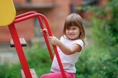 Het meisje beklimt op de dia bij de Speelplaats Stock Foto's