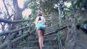 Het meisje beklimt op oude stappen met traliewerk in tropisch park stock video