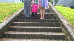 Het meisje beklimt op treden met haar moeder en grootmoeder stock videobeelden