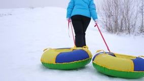Het meisje beklimt sneeuwberg en trekt slee en een opblaasbare sneeuwbuis rust in het de winterpark voor Kerstmis stock videobeelden