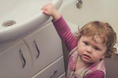 Het meisje bereikt voor de gootsteen in de badkamers Stock Foto's