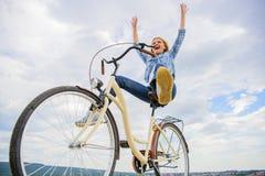 Het meisje berijdt de achtergrond van de fietshemel Vrijheid en verrukking De vrouw voelt vrij terwijl geniet van cirkelend De me royalty-vrije stock fotografie