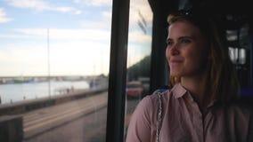 Het meisje berijdt de bus door de kant en kijkt uit het venster stock video