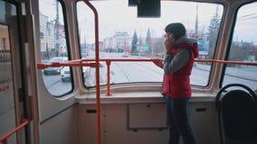 Het meisje berijdt de tram en het luisteren aan muziek stock video
