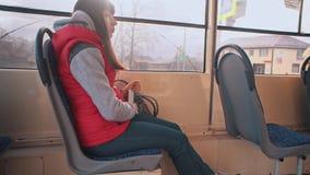 Het meisje berijdt de tram en het luisteren aan muziek stock footage