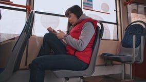 Het meisje berijdt de tram en het luisteren aan muziek stock videobeelden