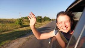 Het meisje berijdt een auto trekt haar uitdeelt van het venster en de lach, golvend haar hand op een hete de zomerdag Langzame Mo stock video