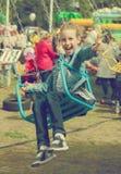 Het meisje berijdt een carrousel Stock Foto
