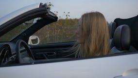 Het meisje berijdt een convertibel wit stock footage