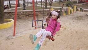 Het meisje berijdt een schommeling in het Park op de Speelplaats stock footage