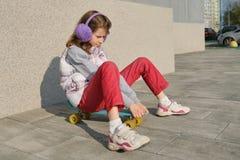 Het meisje berijdt een skateboard, op gebied dichtbij het huis, lentetijd, grijze muurachtergrond royalty-vrije stock fotografie